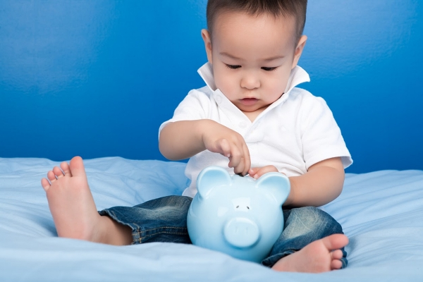 baby boy sitting with blue piggy bank.