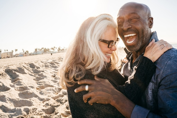 Senior couple laughing on the beach in retirement